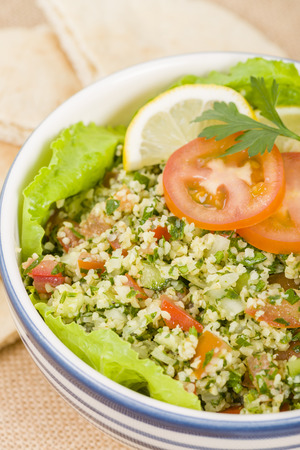 tabbouleh: Tabbouleh - Arabic salad made with bulghur wheat, tomato, cucumber, onions, parsley and min and seasoned with lemon juice and olive oil served with pita bread. Stock Photo