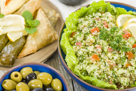 tabbouleh: Mezze - Selection of Middle Eastern dishes. Tabbouleh, falafel, olives, sarma, spinach borek, fatayer, hummus and pita bread.