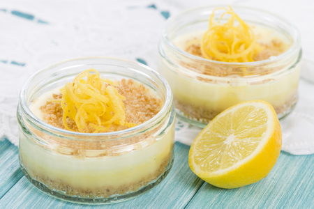 glass topped: Lemon Cheesecake - Individual lemon cheesecakes with biscuit base and whipped cream topped with lemon rind in glass bowls.