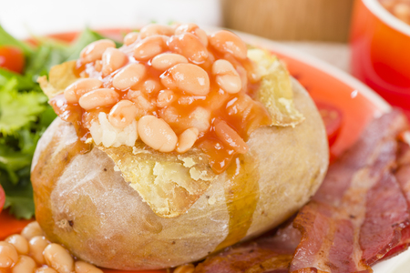 jacket potato: Jacket Potato - Baked potato topped with cheese and baked beans served with salad. Stock Photo