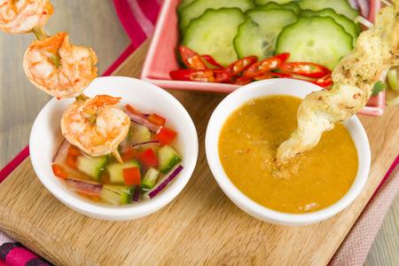 thai food: Sate Gai  Sate Goong - Thai chicken and prawn satays served with cucumber and onion relish and peanut sauce.