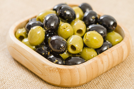 olive green: Olives - Bowl of pitted black and green olives.