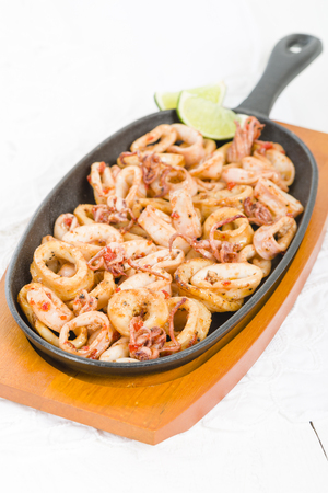 sizzle: Fried Squid Rings - Fried squid rings with red pepper in a sizzle pan. Stock Photo