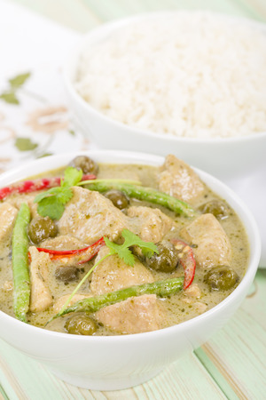 baby rice: Gaeng Khiao Wan Gai - Thai green chicken curry with baby aubergines and snake beans served with steamed jasmine rice. Stock Photo