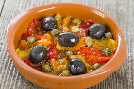 cazuela: Pimientos Asados - Spanish roasted pepper salad with olive oil, vinegar, garlic, capers and black olives. Traditional tapas dish.
