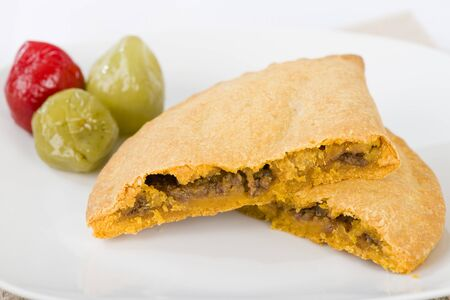 short crust pastry: Caribbean Lamb Pattie - Jamaican spicy minced lamb with onions and peppers in short crust pastry and scotch bonnet chillies on a white background. Stock Photo