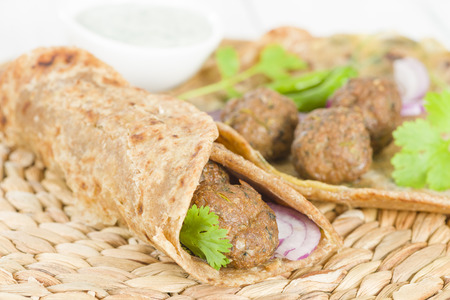 Kati Roll - Kofta kebabs and red onion pickle rolled in a paratha fried with eggs. Indian street food. Imagens