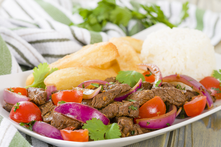 chien: Lomo Saltado - Traditional Peruvian stir-fry with beef, red onions, tomatoes and fries garnished with parsley and coriander.