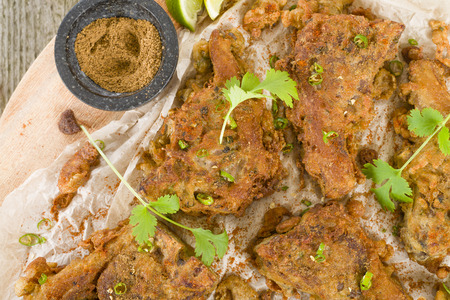 battered: Mutton Chaap - Fried battered spicy lamb cutlets garnished with green chilies, coriander and chaat masala.