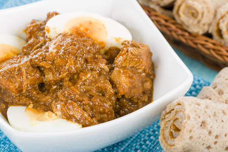 ethiopian: Doro Wat - Ethiopian red chicken stew cooked with onions and berbere chili and spices mix, topped with hard-boiled eggs. Served with injera.