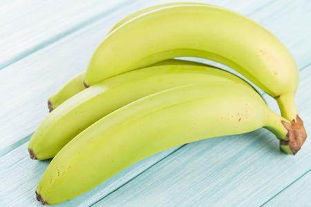 unripened: Green Bananas - Unripened bananas on a blue wooden background.