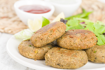 grilled food: Shami Kebab - Minced meat and chana dal patties stuffed with red onion pickle and served with salad, lemon wedges, chilli sauce and mint raita, South Asian  Middle Eastern cuisine. Stock Photo