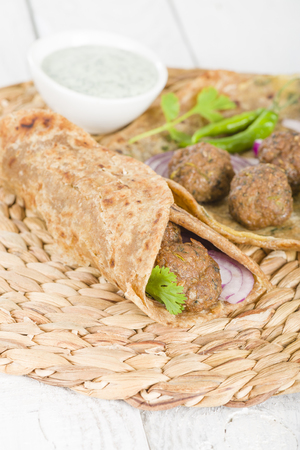 paratha: Kati Roll - Kofta kebabs and red onion pickle rolled in a paratha fried with eggs. Indian street food. Stock Photo