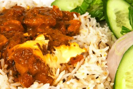 Traditional Indian butter chicken curry with jeera (cumin) rice and a salad.