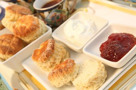 A traditional British cream tea, with scones (biscuits), strawberry jam, cream and tea. Stock Photo