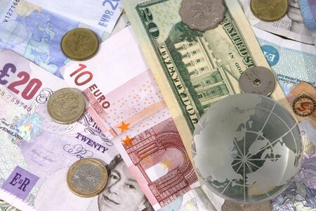 Globe on top of a variety of different currency notes and coins, representing foreign exchange (similar to another image but the sharpest focus is on the globe) Stock Photo