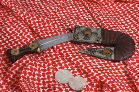 iraq money: Arab dagger with Maria Theresia taler coins on a keffiyah headscarf.