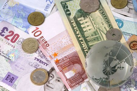 Globe on top of a variety of different currency notes and coins, representing foreign exchange (similar to another image but the sharpest focus is on the currency)