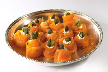 Smoked salmon canapes, filled with cheese and topped with a caper.