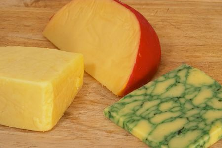 cheeses: Board with three cheeses, gouda, sage derby and cheddar