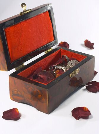 A laquered, lined jewel box containing dried rose petals and silver jewellery.