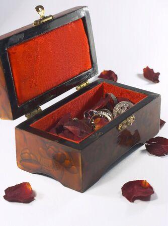 laquered: Un laccato lucido, fiancheggiato gioiello scatola contenente petali di rosa appassita e gioielli d'argento.