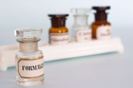 A bottle of formalin, or formaldehyde, in front of a tray of medical bottles. All antique.