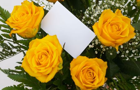 A bouquet of yellow roses with a blank gift tag. photo