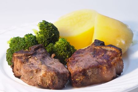 Two lamb chops, grilled with herbal marinade, served with boiled potatoes and brocolli Stock Photo