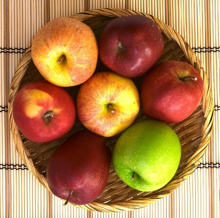 A basket of different varieties of apples: granny smith, red delicious, royal gala and pacific rose