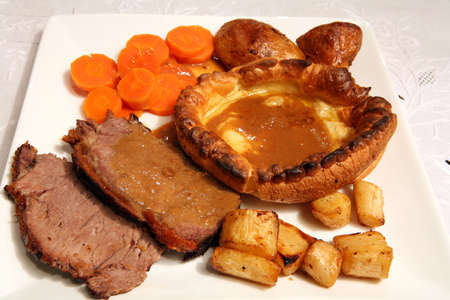 Sunday lunch of roast sirloin beef, Yorkshire pudding, boiled carrots, roast potatoes and roast parsnips with gravy photo