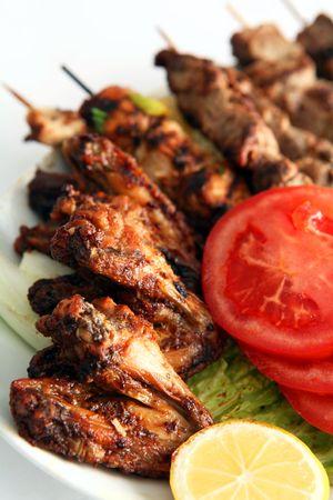 alitas de pollo: Alas de pollo con kebabs en un plato adornado con ensalada. Foto de archivo