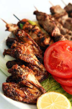 and chicken wings: Chicken wings with kebabs on a plate garnished with salad.