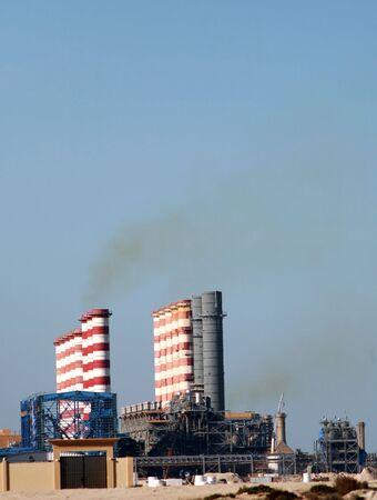 desalination: Smoke stacks on a desalination plant belching sulphurous fumes. Stock Photo