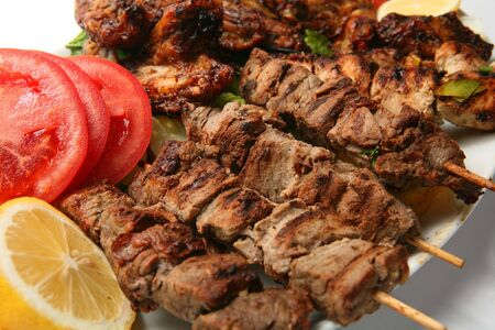A plate of chicken and lamb kebabs and chicken wings, served with a garnish of lemon, tomato and lettuce.