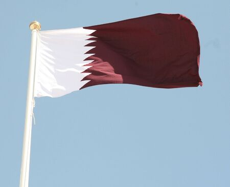 The maroon and white national flag of the Arab Gulf State of Qatar.