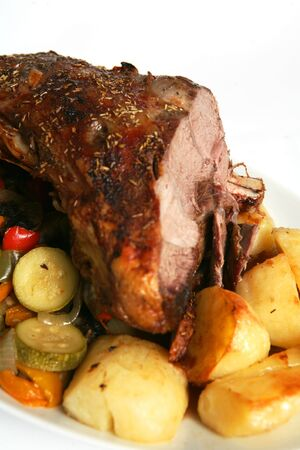 Herbed roast lamb with roast potatoes and stir-fried vegetables. Stock Photo