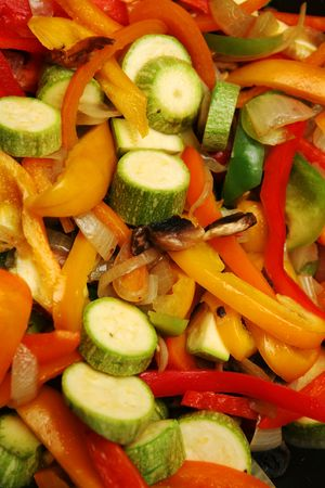 A vegetable stir-fry in a wok, with strips of red, yellow, green and orange bell pepper, mushroom, courgette and onion Stock Photo