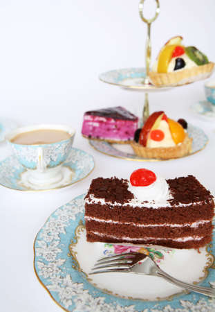 A slice of chocolate cake tempting the palate at teatime. Other cakes are offered on the traditional cake-stand. photo
