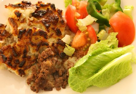 minced pie: Shepherds pie and salad, traditional British home-cooking. Stock Photo