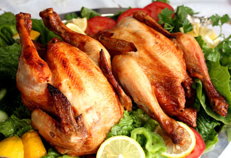 Buffet with two grilled chickens on a bed of salad.