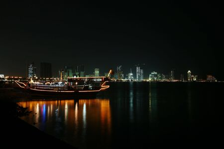 A pleasure dhow on the Corniche in Doha, Qatar, at night, against the high-rise skyline. January 2007 Stock Photo - 809855