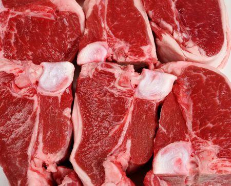 A display of raw lamb loin chops, macro. photo