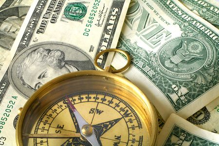 A compass, its needle pointing South, on an assortment of US banknotes, symbolic of loss, risk or a bad investment