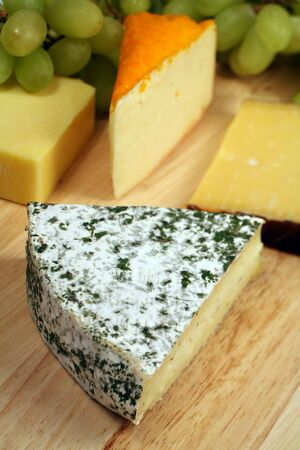 cheeseboard: A gourmet cheeseboard, focus on a wedge of herb-coated Reverend Brie.