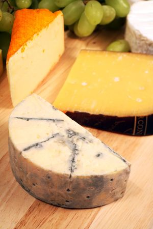 tabla de quesos: Un brie con sangre azul suave muy maduro en un cheeseboard con quesos y uvas de Gouda portuario de Salut, del camembert y de Amsterdam. Foto de archivo
