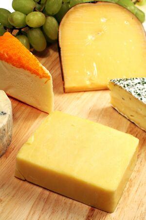tabla de quesos: Un cheeseboard gastr�nomo bien-provisto con Cheddar a la delantera.