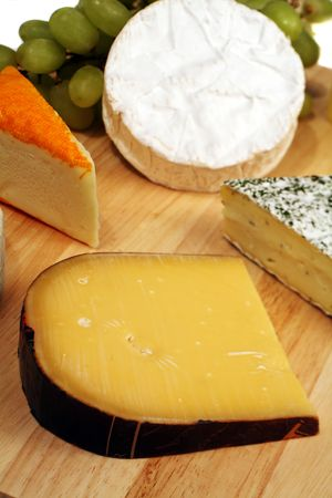 cheeseboard: Old Dutch gouda with camembert, brie, port salut and grapes on a gourmet cheeseboard.  Stock Photo
