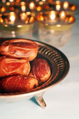 Big dates on a silver tray, with gold rimmed Arab coffee cups in the background. A traditional ramadan fast-breaking treat.