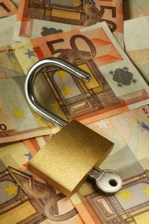 billets euros: Un cadenas ouvert sur un fond des notes de 50 euros, symbolique de la richesse ouvrante. Banque d'images